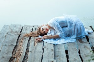 Beautiful girl with sad face lying on a wooden pier.
