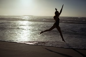 Woman jumping on beach