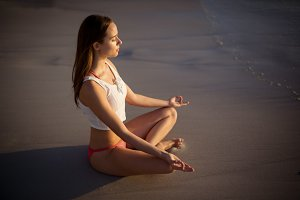 Beautiful woman performing yoga on beach