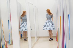 Shopping for woman. A woman in a new dress looks at herself in the mirror