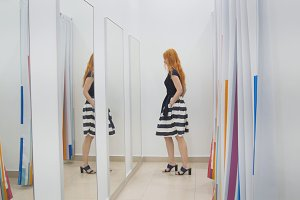 A girl trying on a dress in front of a mirror in a women's clothing store