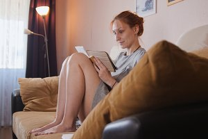 A girl is sitting on the couch with a tablet computer in hands