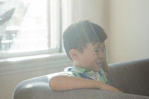 Boy sitting on sofa in living room