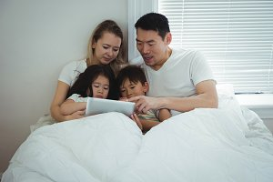 Family using digital tablet in bedroom