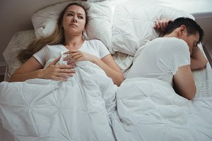 Worried woman lying while man sleeping beside her in bedroom