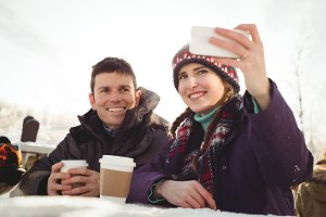 Happy Skier couple clicking a selfie
