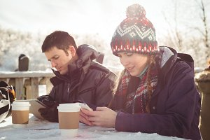 Happy skier couple using mobile phone and digital tablet at table