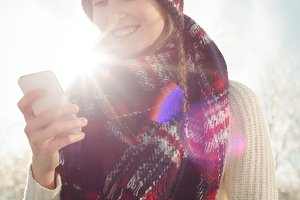 Smiling woman in winter wear typing a text message