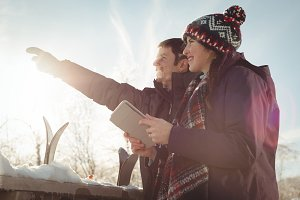 Skier couple with digital tablet looking at a distance
