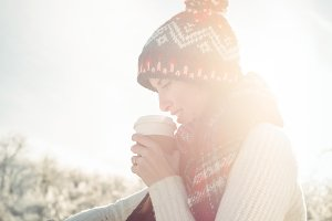 Woman skier watching her smartwatch while having coffee