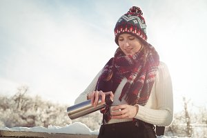 Beautiful woman in winter wear pouring drink in cup