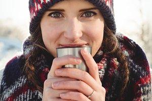 Beautiful woman in winter wear having a drink in cup