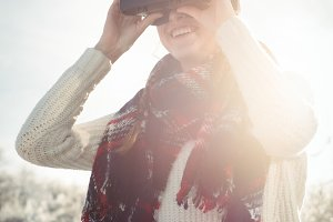 Woman in winter wear using VR headset