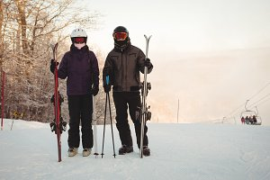 Skier couple with skies standing on snowy landscape