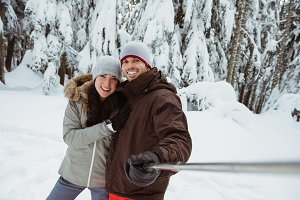 Skier couple taking a selfie on snow covered mountain