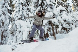 Female snowboarder jumping over the slope