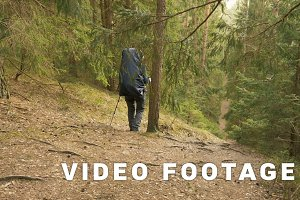 Girl hikes in the summer forest - flying camera shot