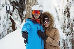 Skier couple taking a selfie on snowy landscape