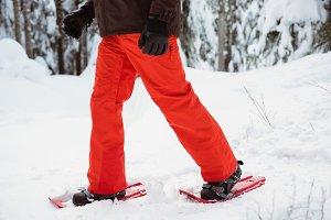 Skier walking with snow shoe on snowy landscape