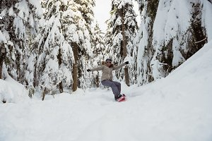Woman snowboarding on snowy mountain