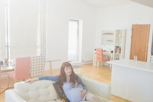Thoughtful pregnant woman relaxing on sofa in living room