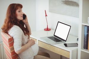 Pregnant woman talking on mobile phone in study room