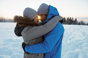 Couple embracing each other on snowy landscape