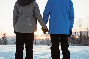 Couple standing and holding hands on snowy landscape