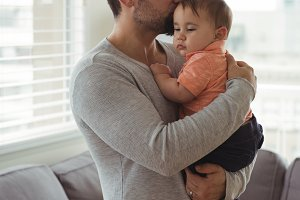 Father kissing his baby in living room