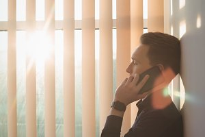Male executive talking on mobile phone near window blinds