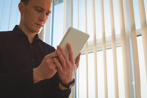 Male executive using digital tablet near window blinds