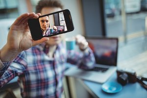 Male executive taking selfie from mobile phone