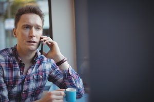 Male executive talking on mobile phone while having coffee