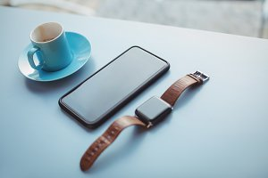 Wristwatch, mobile phone and cup of coffee at counter