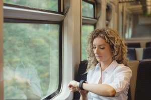 Woman checking time on her watch while travelling