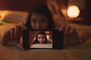 Woman taking selfie on mobile phone in bedroom