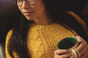 Thoughtful woman sitting and having coffee on sofa