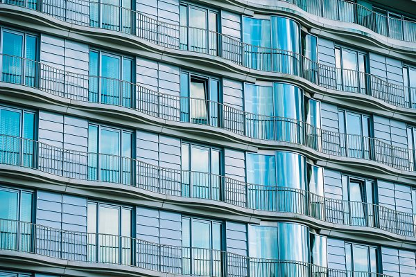 Modern glass building with railing…