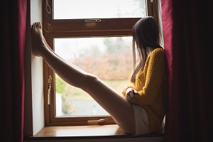 Woman sitting at window sill and looking outside