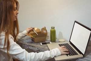 Woman using laptop while eating salad