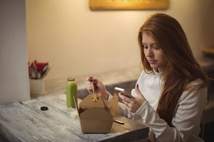 Woman using mobile phone while eating salad