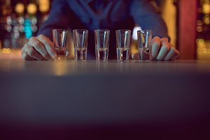 Bartender placing shot glasses in a row at counter