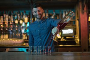 Bartender pouring alcoholic drink in shot glasses