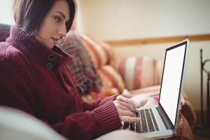 Beautiful woman using laptop on sofa