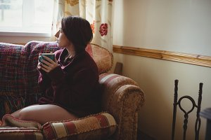 Thoughtful woman sitting and holding a coffee cup
