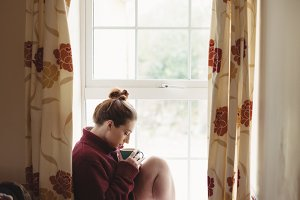 Woman sitting at window sill and having coffee