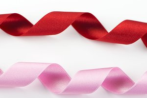 Pink and red ribbons on white background. Horizontal shoot. Isolated. Copy space.