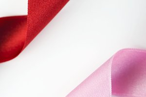 Pink and red ribbons on white background. Vertical shoot. Isolated. Copy space.