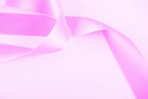 Pink ribbon on white background. Horizontal shoot. Isolated. Copy space.