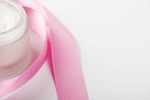 Bottle of cream for face next to pink ribbon on white background. Isolated. Copy space.